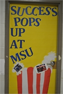 "Alumni Pride:  ""A College themed door Welcomes our students to the Classroom"""