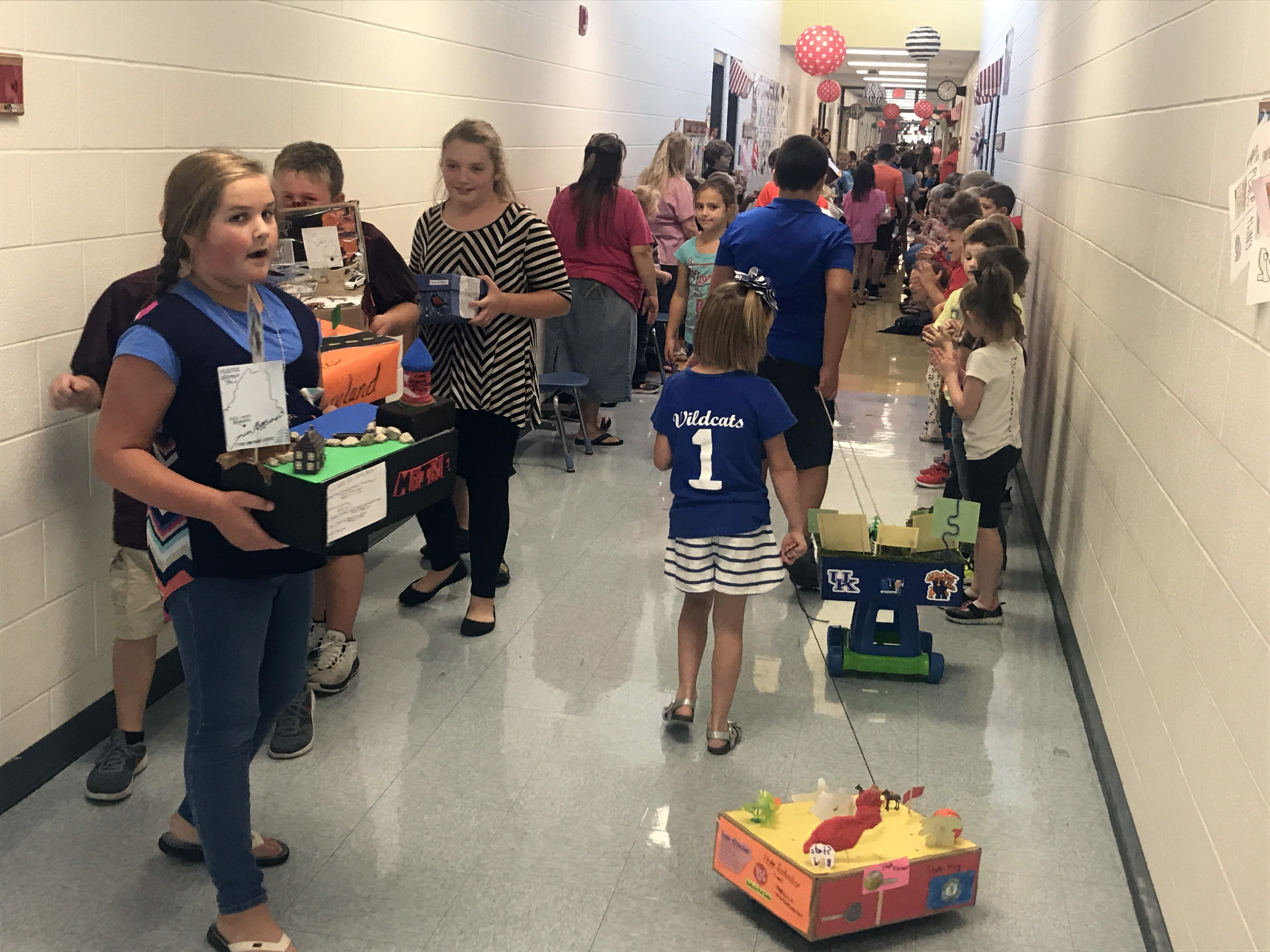Students parade their states floats down the main hallway while classrooms line up along the parade route.